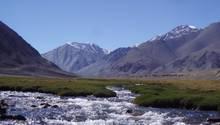 Ein breiter Wildbach fließt durch einen Talboden, im Hintergrund erheben sich Berge, darüber blauer Himmel