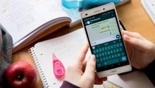 Eine Schülerin hält ein Smartphone