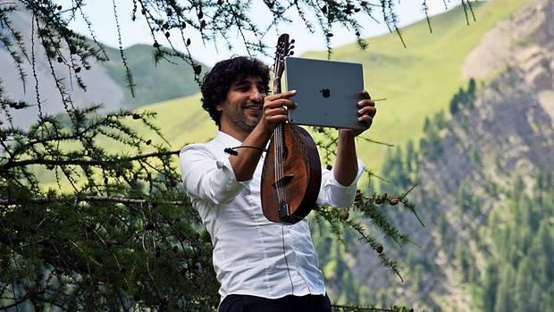 Avi Avital hat auf seinemiPad nicht nur alle Noten, erfotografiert damit auch das Publikum und die Landschaft, um seine Bilder und Clips später auf Facebookund Instagram hochzuladen.