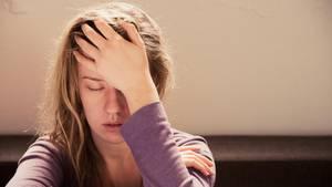Eine junge Frau fasst sich an den Kopf