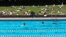 Belästigung zweier Frauen durch Männergruppe: Zu sehen ist eine Schwimmbadszene mit gefüllter Liegewiese