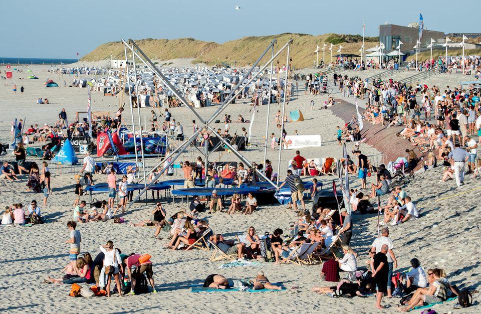 Strandleben auf Norderney:Touristen sitzen in der Abendsonne.