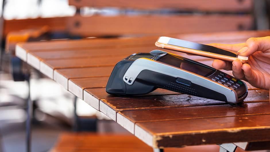 Ein iPhone mit Apple Pay zahlt in einem Restaurant-Terminal