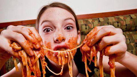 Kind isst Spaghetti mit den Händen