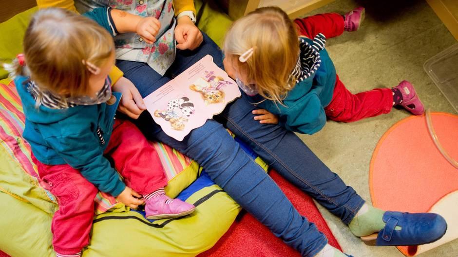 Kinder schmökern mit ihrer Kita-Erzieherin in einem Bilderbuch