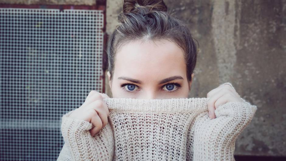 Eine junge Frau, die sich ihren Pulloverkragen über die Nase zieht