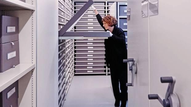 """Soizic Pfaff wirft einen Blick in die Boxen, in denen Stoffproben und Zeichnungen lagern. Die wichtigsten Stücke der Sammlung befinden sich im """"Safe"""""""