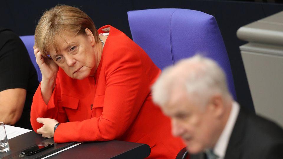 Im Bundestag stützt Angela Merkel ihren Kopf auf, während Horst Seehofer im Vordergrund am Rednerpult steht