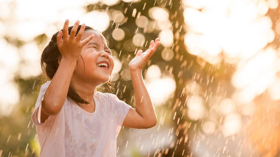 Kleines Mädchen freut sich über Regen