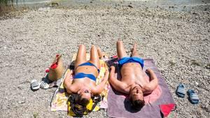 Auf zwei Baedtüchern liegen eine Frau und ein Mann in Badesachen nebeneinander auf einem Kiesstrand. Am oberen Bildrand der See