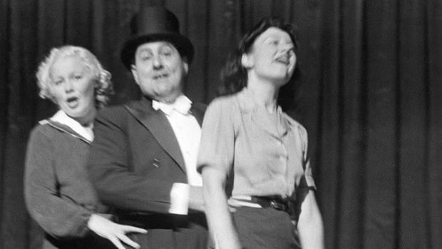 Ein Mann mit Zylinder zwischen zwei jungen Frauen auf der Bühne