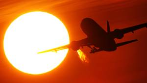 Ein Flugzeug hebt ab. Es fliegt in einen von der Sonne geröteten Himmel hinein