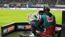 """Ein Kameramann filmt die Bundesliga. Auf der Bande um ihn herum steht """"Sky Sport""""."""
