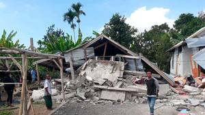 Mann steht vor vom Erdbeben zerstörtem Haus auf der indonesischen Ferieninsel Lombok