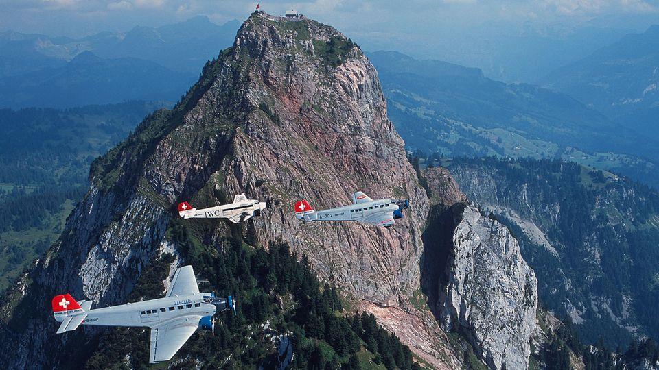 Drei Flugzeuge vom Typ Junkers JU 52im Formationsflug über den Bergen.