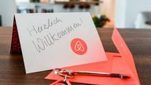 Ein Schlüssel mit einem Airbnb-Anhäger und eine Herzlich-Willkommen-Karte liegen in der Wohnung eines Gastgebers.