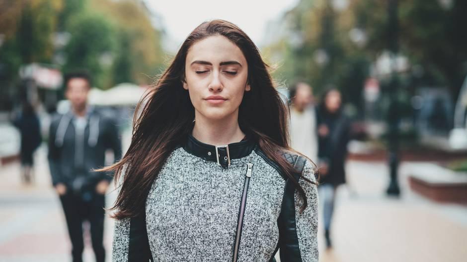 Sexuelle Belästigung: Frau mit geschlossenen Augen auf der Straße