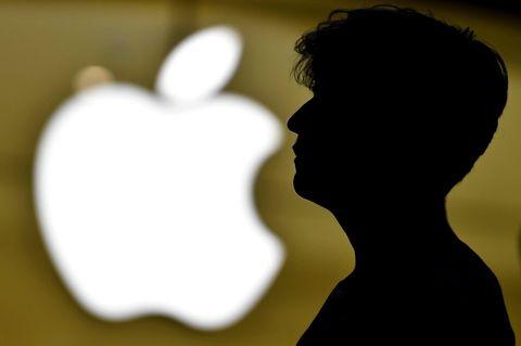 Ein Mann steht vor dem Logo von Apple