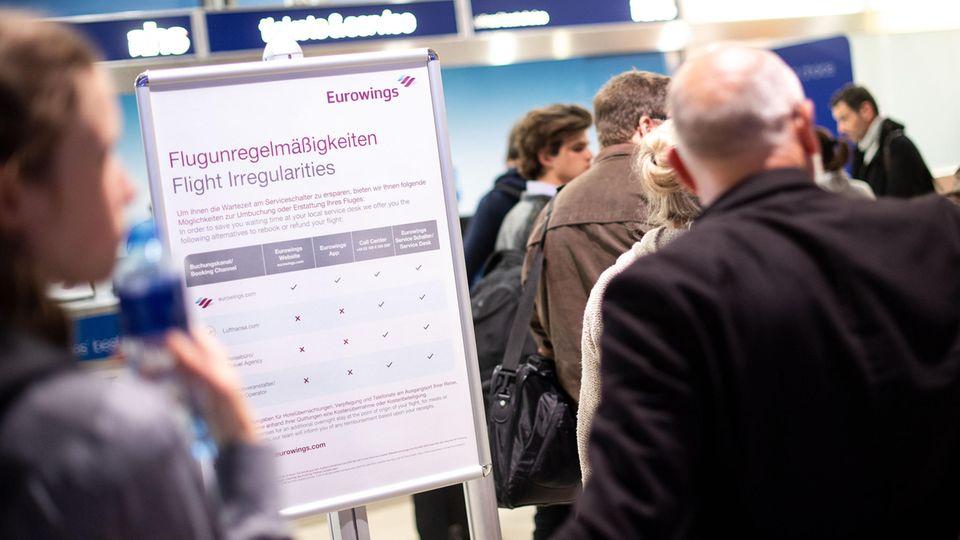 Reisende warten am Flughafen vor einem Schalter von Eurowings auf Umbuchungsmöglichkeiten.