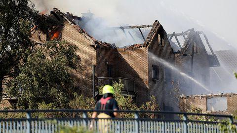 Ein Feuerwehrmann geht an einem hellen Backsteinhaus vorbei, dessen Dachstuhl brennt. Ein anderer löscht.