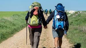 Zwei Pilger gehen Hand in Hand auf dem Jakobsweg Santiago de Compostela entgegen. Sie haben große Rucksäcke auf dem Rücken