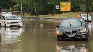 Im hessischen Stadtallendorf stehen Pkw auf einer nach einem kurzen und starken Regenguss überfluteten Straße. Die Regenmassen hatten ganze Straßenzüge überflutetet, Gebäude standen im Keller ebenfalls unter Wasser