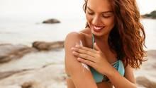Eine Frau cremt sich am Strand ein