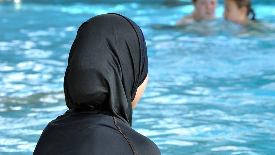 Burkini oder Burka – Frau schaut im Schwimmbad aufs Becken