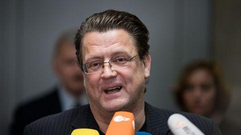 Stephan Brandner, ein Mann mit Brille und zurückgegelten braunen Haaren, spricht in die Mikrofone mehrerer TV-Sender