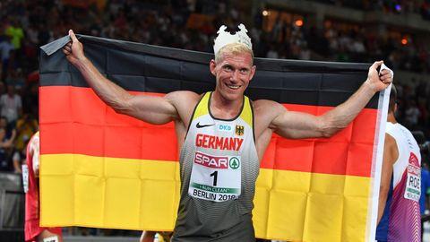 Zehnkämpfer Arthur Abele jubelt mit einer Pappkrone auf dem Kopf und einer Deutschland-Flagge in den ausgebreiteten Armen