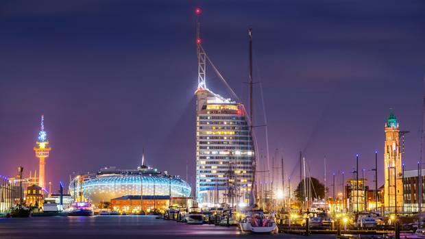 Das neue Bremerhaven bei Nacht: das Klimahaus 8 Grad Ost in Bildmitte und das hohe Hotel Atlantic Sail Cityrechts daneben.
