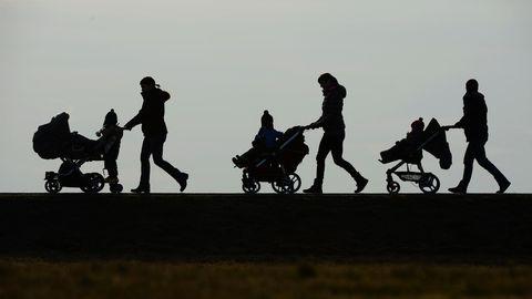 Im Gegenlicht sind die Umrisse dreier Frauen mit Kinderwagen zu sehen. Sie schieben ihre Kinder von rechts nach links