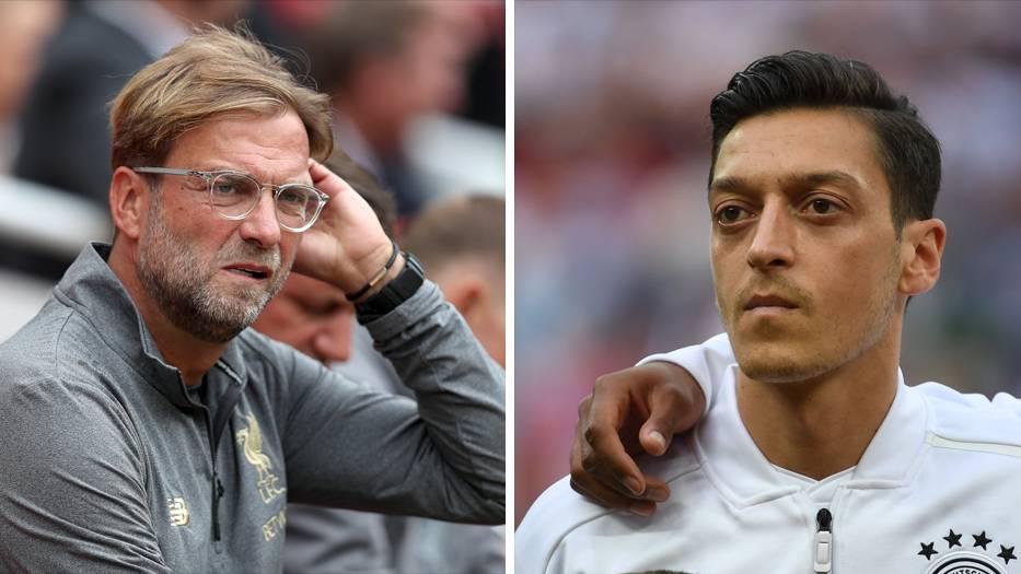 Links sitzt Jürgen Klopp auf einer Trainerbank und streicht sich mit links durchs Haar. Rechts steht Mesut Özil bei der Hymne