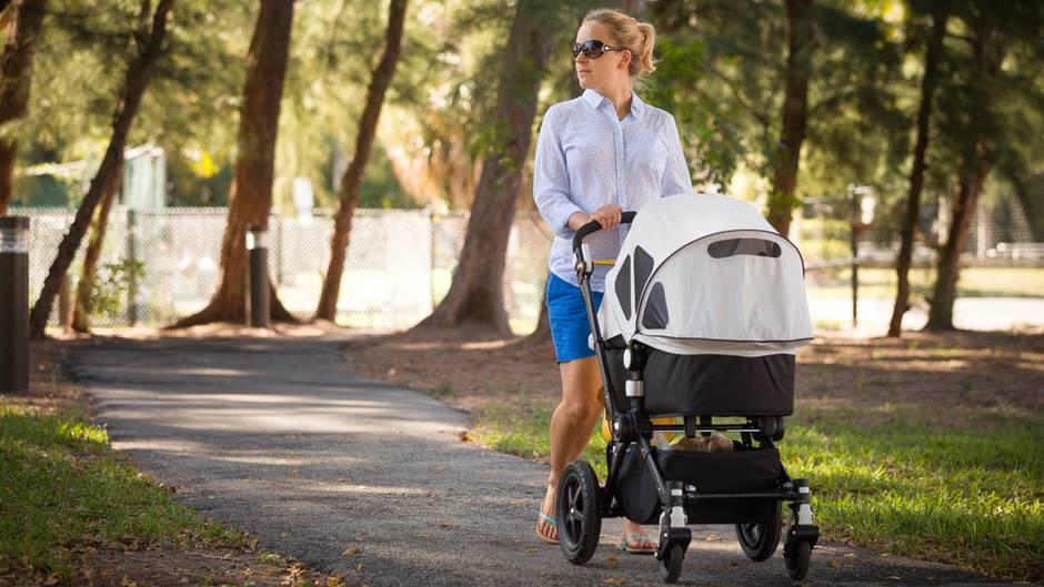 Eine junge Mutter schiebt einen Kinderwagen durch einen Park
