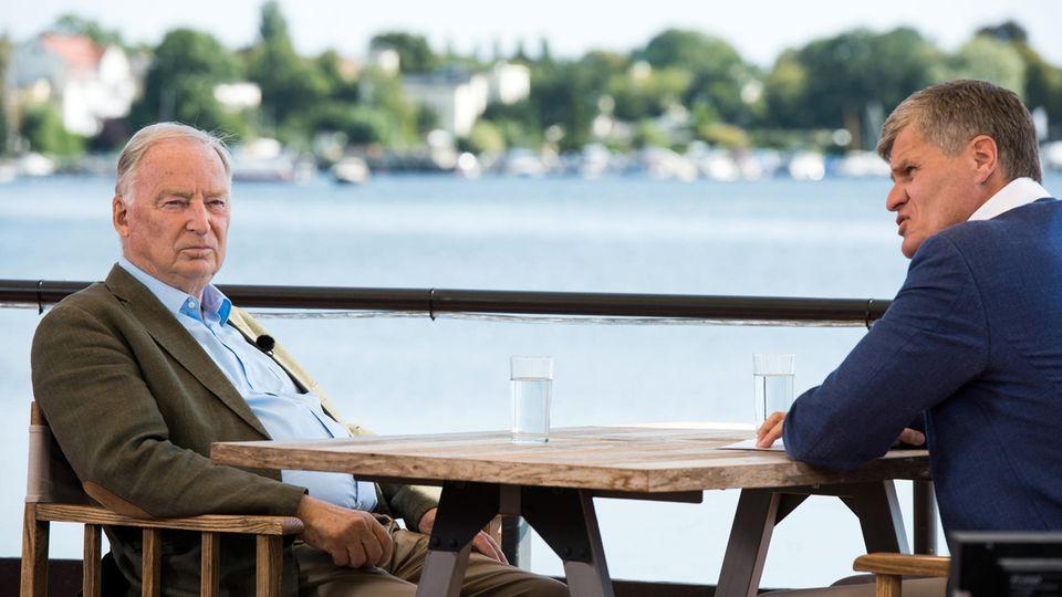 An einem Holztisch sitzen Alexander Gauland von der AfD und Journalist Thomas Walde von ZDF. Im Hintergrund glänzt ein See