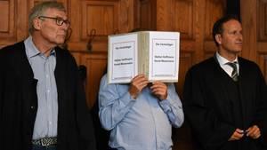 Bremen: Der wegen Mordes Angeklagte hält einen Schnellhefter vor sein Gesicht