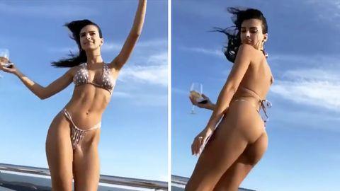 Supermodel Emily Ratajkwoski tanzt im knappen, gepunkteten Bikini auf einer Yacht und hält ein Weinglas in der Hand