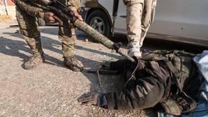 Ein toter Kämpfer der Terrororganisation Islamischer Staat wird von irakischen Soldaten überprüft