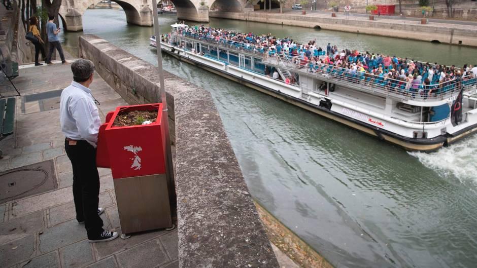 """Ein Mann steht am Ufer der Seine und uriniert in ein """"Uritrottoir"""""""