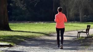 Eine Joggerin joggt durch einen Park