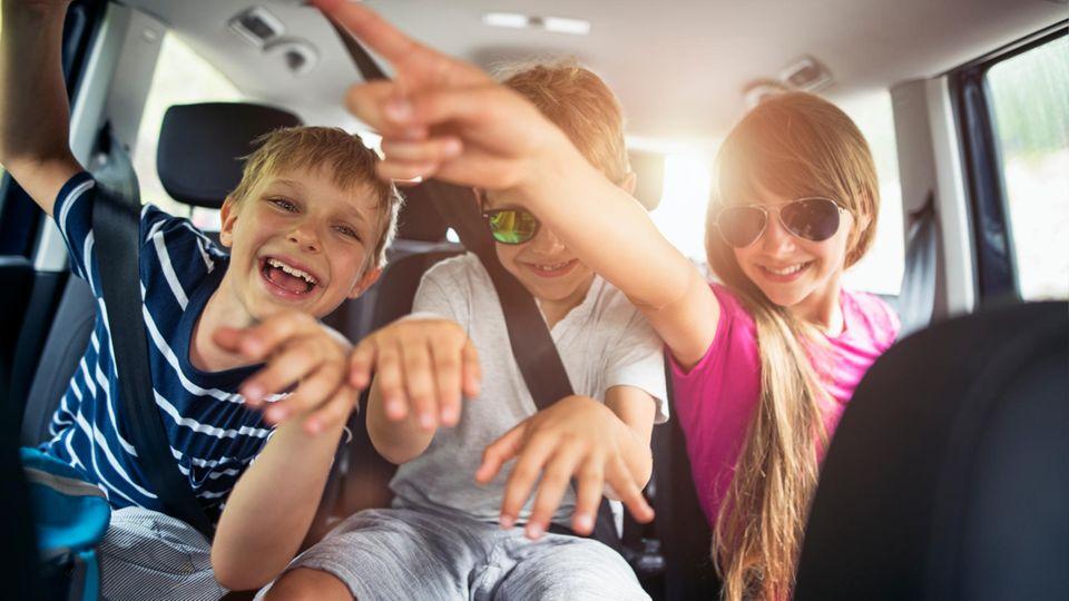 Drei Kinder sitzen auf der Rückbank eines Autos und machen Star-Posen