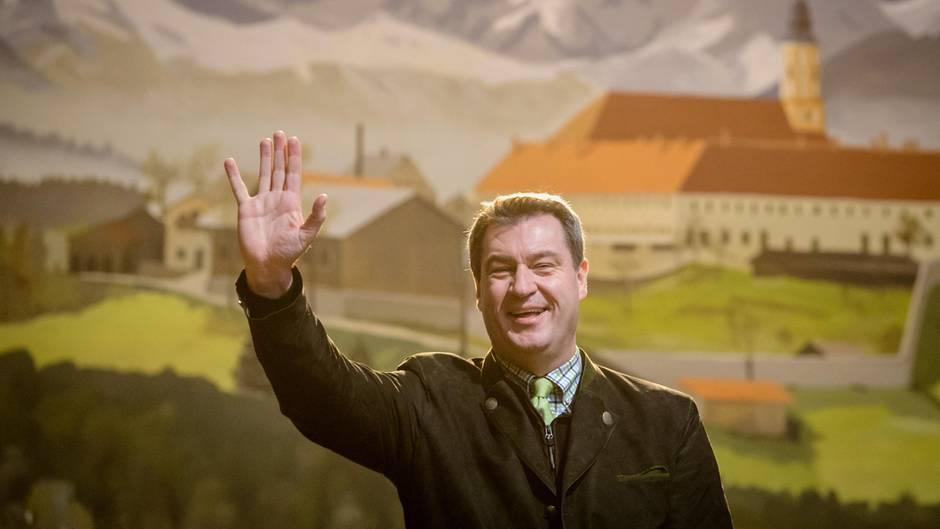 Vor einer gemalten bayrischen Landschaft mit Bergen und Kloster steht Markus Söder im Janker und winkt