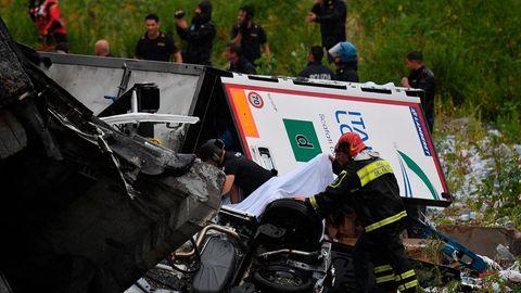 Feuerwehrleute suchen zwischen zerstörten Autos und großen Betonteilen nach Opfern des Einsturzes einer Autobahnbrücke in Genua