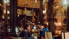 Ein Mann und eine Frau sitzen sich an einem Café-Tisch gegenüber