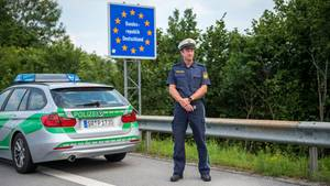 Ein Beamter der bayerischen Grenzpolizei steht hinter seinem Dienstwagen an einem Grenzübergang