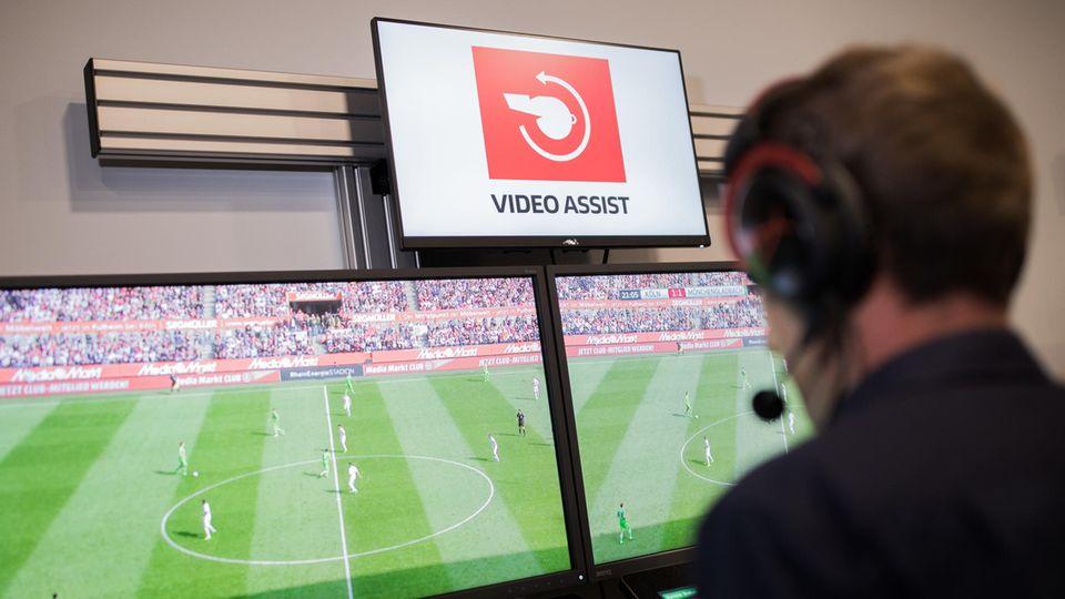 Der Video-Schiedsrichter sitzt vor vier Monitoren auf denen Fußball läuft
