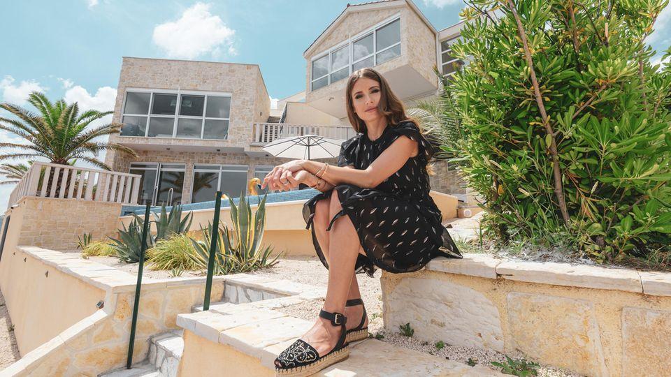 Fernsehmoderatorin Cathy Hummels sitzt vor ihrer Luxusvilla CaMa