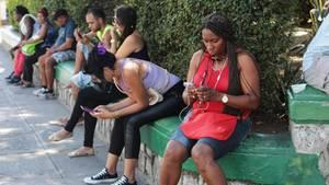 Kubaner sitzen an einem Wifi-Hotspot und surfen im Internet