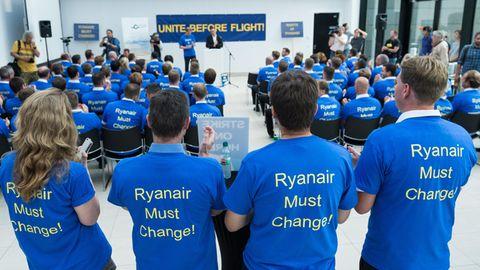 """Beschäftigte der Fluggesellschaft Ryanair tragen im Main Airport Center bei einer Demonstration für bessere Arbeitsbedingungen T-Shirts mit der Aufschrift """"Ryanair Must Change!"""""""