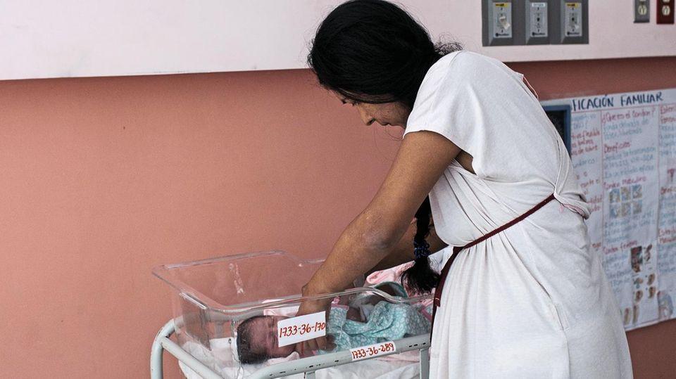Eine Mutter versorgt ihr Neugeborenes im Nationalen Frauen-Hospital in San Salvador. Ärzte in öffentlichen Krankenhäusern müssen Frauen auch bei Fehlgeburten melden